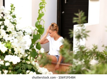 Portrait of  depressed  woman sitting on stairs at home.Crying woman.Using smart phone.