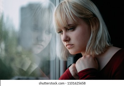 Portrait of depressed young blond woman near window at home. Sadness, nostlagic, depression.