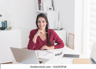 Portrait of an designer working home on new ideas. A dark hair woman in her 30's is sitting at a white table in casual clothes, she is looking at camera holding a pencil after drawing a new sketch