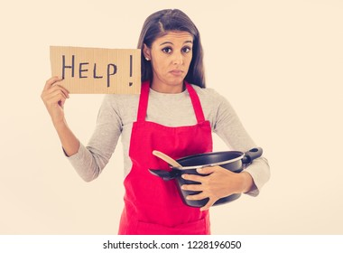 Portrait of desperate helpless inexperienced home cook woman asking for help wearing red apron learning to cook in cooking classes isolated on white background.