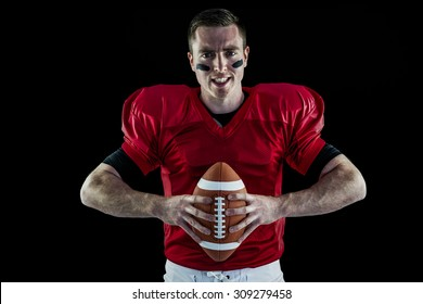Portrait of a determined american football player holding a ball