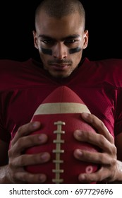 Portrait of determined American football player holding a football with both his hands