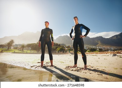 Portrait of a determined male and female triathletes looking into the distance. Young man and woman standing at the beach wearing wetsuit ready for triathlon competition.