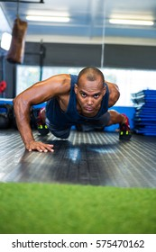 Portrait of determined man doing push-ups in gym
