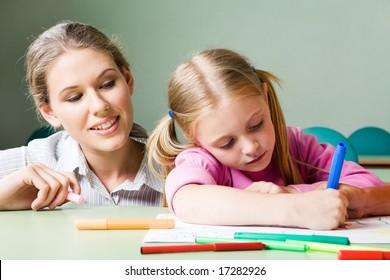 Portrait of diligent girl drawing something under tending of her teacher