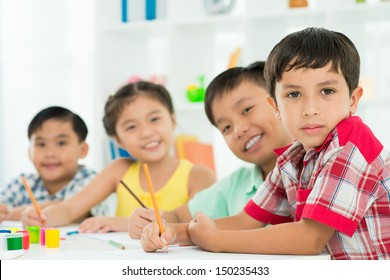 Portrait of diligent pupils sitting at the school desk