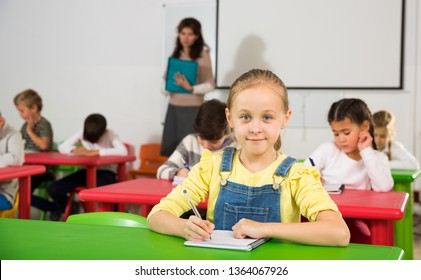Portrait of diligent schoolgirl writing exercises at lessons in primary school