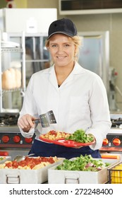 Portrait Of Dinner Lady Serving Meal In School Cafeteria