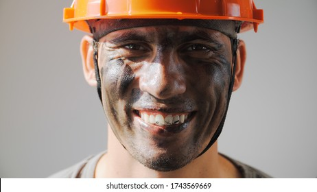 Portrait Dirty Mine Worker. Beautiful Caucasian Man in a Hard Hat Smiles. Filthy Job and Physical labor. Coal Mining. People Working Equipment. Close up