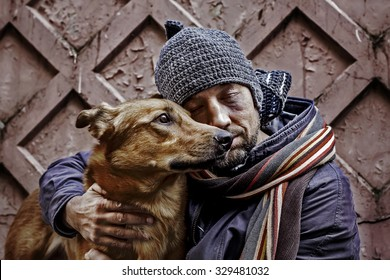 Portrait of dirty tramp with closed eyes and his dog. Image with toning and selective focus