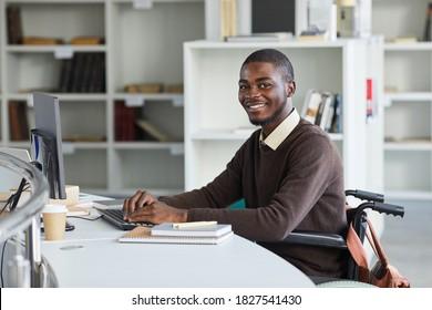 Porträt eines behinderten afroamerikanischen Mannes, der Computer nutzt und beim Studium in der Universitätsbibliothek, Kopienraum mit der Kamera lächelt