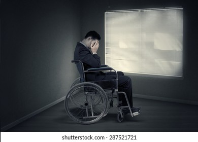 Portrait of disabled entrepreneur looks sad and sitting in wheelchair near the window