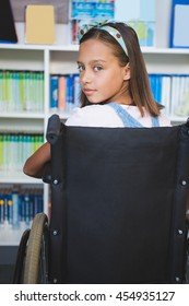 Portrait of disabled schoolgirl in library at school
