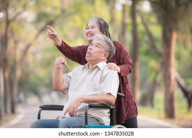 Portrait of Disabled senior man sitting on wheelchair with caring wife on park. Lifestyle and Healthcare elderly retirement concept.