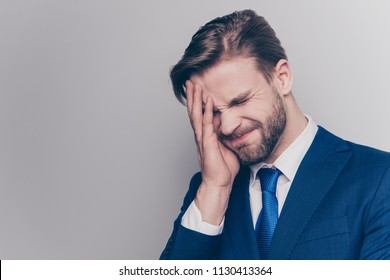 Portrait of disappointed, upset man with stubble in blue suit, cover half face with palm, isolated on grey background, forget something important to do, emotion after divorce, failure