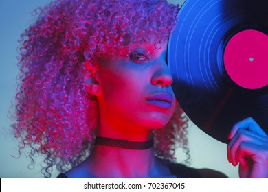 portrait of a disco woman holding a retro vinyl with eighties music and neon light