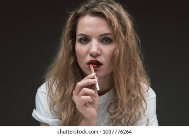 Portrait of discontented blonde woman with wound on her lips, she is holding cigarette and looking at camera. Isolated on background