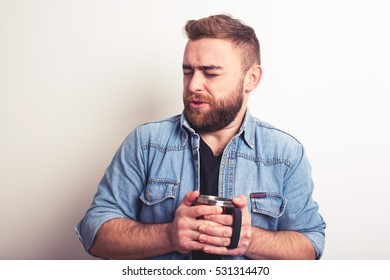 Portrait of disgusted man tasting something from cup
