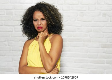 Portrait of disgusted woman, hispanic girl showing disgust for bad smell or taste.