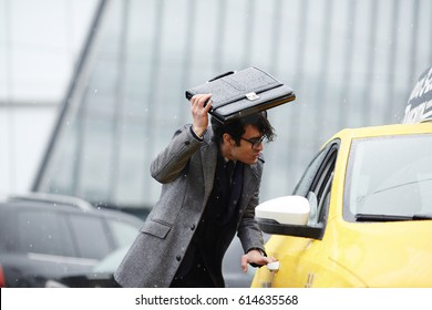 Portrait of disheveled Middle-Eastern businessman hurrying to catch taxi cab on rainy autumn street, covering head with briefcase