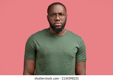 Portrait of displeased African American guy frowns face, has gloomy expression, discontent with bad service in hotel, has dark thick bristle, stands over pink wall. People, negative feelings concept