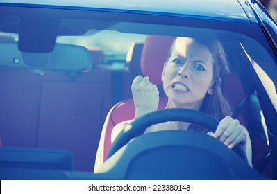 Portrait displeased angry pissed off aggressive woman driving car, shouting at someone in traffic hand fist up in air front windshield view. Emotional intelligence concept. Negative human expression