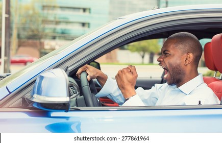 Portrait displeased angry pissed off aggressive man driving car, shouting at someone in traffic hand fist up in air side door view. Emotional intelligence concept. Negative human expression