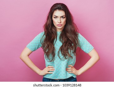 Portrait of displeased upset angry female, being discontent and unhappy as can`t achieve goals, isolated over pink studio background. Dissapointed young woman has troubles. Fashion Lifestyle Beauty