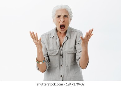 Portrait of dissatisfied furious and angry grandmother with white hair in casual shirt raising palms in clueless gesture shaking hands and yelling frowning feeling anger and fury while arguing