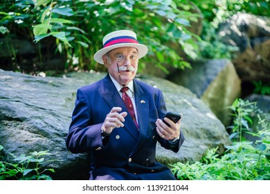 Portrait of a distinguished, well-dressed old gentleman in a suit sitting in the park and using his smartphone to text, sms or message someone. He is wearing a monocle and looks happy.