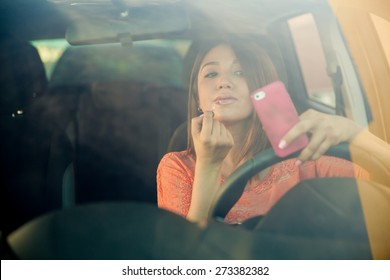 Portrait of a distracted young woman looking at her smartphone and putting some lipstick on while driving a car