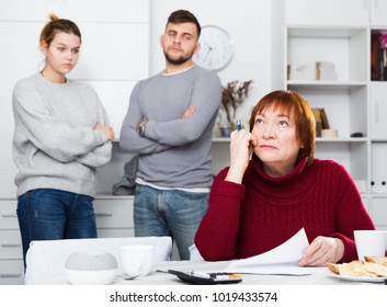 Portrait of distressed aged woman with paperwork at home table with irritated family behind her