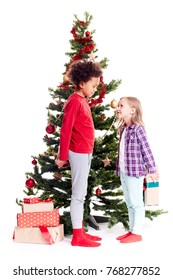 Portrait of diverse brother and sister standing near Christmas tree, girl hiding gift box behind her back