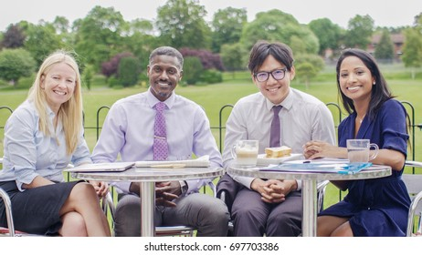 Portrait of diverse business team smiling to camera whilst outdoors during a meeting