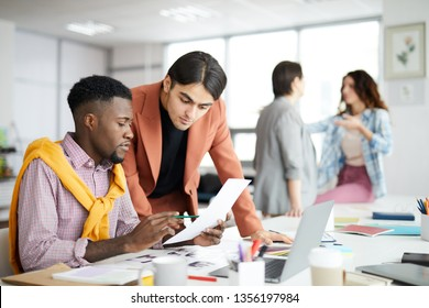 Portrait of diverse business team working in modern office with focus on African-American man holding document, copy space