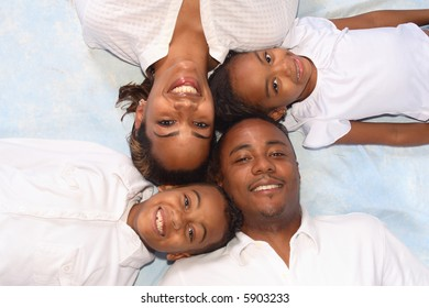 A portrait of a diverse family of four laying on the floor, picture taken from above.
