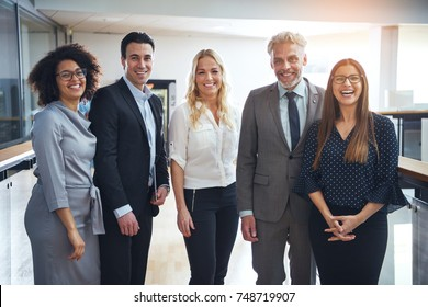 Portrait of a diverse group of confident business colleagues smiling and standing together in the hallway of a modern office
