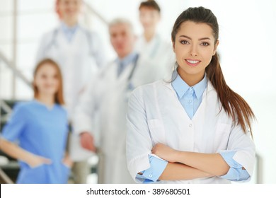 Portrait of doctor in front of colleagues indoors