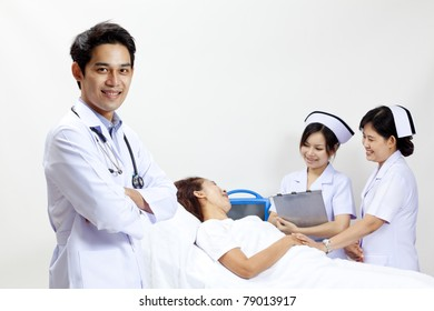 Portrait of a doctor with his co-workers talking with a patient in the background