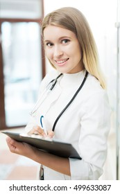 portrait of a doctor, holding a stethoscope. Young woman doctor.Doctor holding a folder and pen