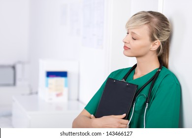 Portrait of doctor leaning on the wall with closed eyes