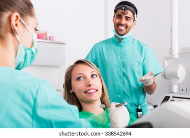 Portrait of doctor and positive russian patient at dental clinic