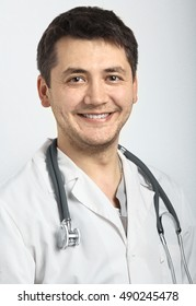 Portrait of a doctor with a smile, gray background. Pretty man.