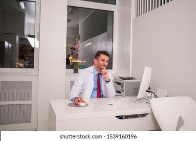 Portrait of Doctor specialist sitting on a chair at his desk while working and smiling