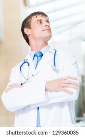 Portrait of a doctor standing in the office and crossed his arms