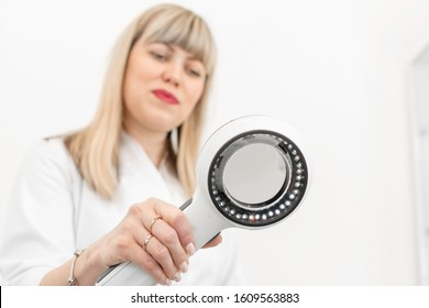 Portrait of a doctor trichologist dermatologist looking at a dermatoscope. Focus on the hand with a dermatoscope, the doctor is blurred. In a bright cosmetology room.