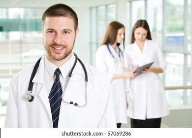 A portrait of doctor with two attractive nurses in the background