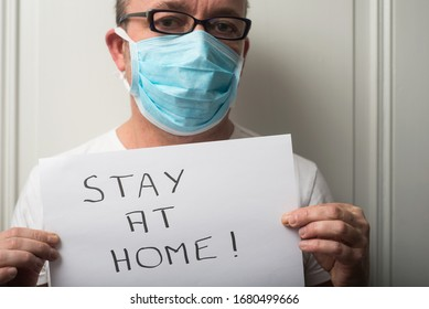Portrait of doctor wearing medical mask to protect against the corona virus with prevention message : stay at home