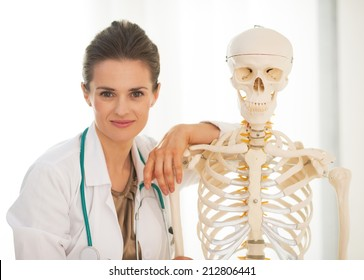 Portrait of doctor woman near human skeleton anatomical model