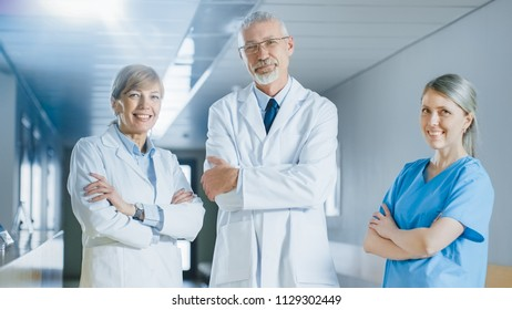 Portrait of Doctors and Nurses Posing in the Hospital Building, Arms Crossed and Smiling. Brilliant People in Medical Professionals who Save Lives.